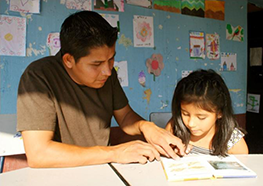 Father helping his daughter to read in a REAULA project school